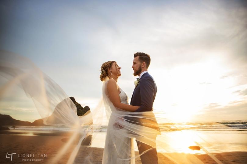 auckland wedding bride and groom piha beach sunset